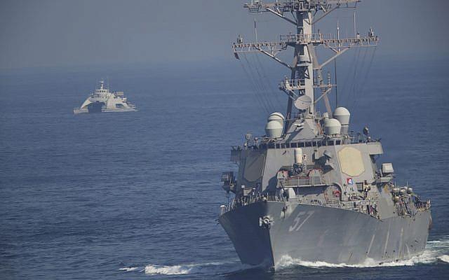 El USS Mitscher, parte de un grupo de ataque liderado por el portaaviones USS John C. Stennis, navega mientras un barco de la Guardia Revolucionaria Iraní lo oculta el 21 de diciembre de 2018. (AP Photo / Jon Gambrell)