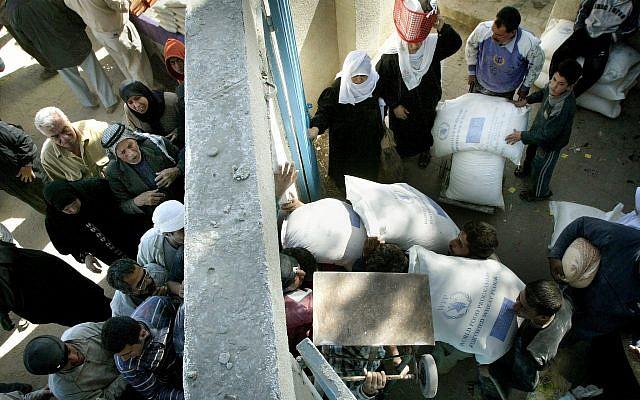 Los palestinos reciben sus suministros mensuales de alimentos del Programa Mundial de Alimentos en la ciudad de Gaza, 4 de marzo de 2006 (Foto AP / Hatem Moussa)