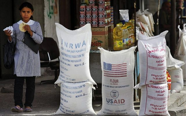 Un estudiante palestino pasa por delante del Organismo de Obras Públicas y Socorro de las Naciones Unidas (OOPS) y la ayuda humanitaria de la USAID el 6 de junio de 2010 en el campamento de refugiados de Shatie, en la ciudad de Gaza. (Foto AP / Lefteris Pitarakis, Archivo)
