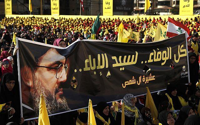 En esta foto del 13 de abril de 2018, los partidarios del líder de Hezbollah, Sayyed Hassan Nasrallah, sostienen una pancarta con su retrato y palabras en árabe que dicen: 'Toda la lealtad al hombre de la nobleza'. (AP / Hussein Malla)