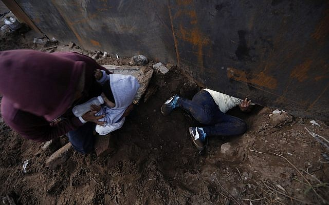 El migrante hondureño Joel Méndez, de 22 años, se fue, alimenta a su hijo Daniel de ocho meses de edad, mientras que su compañera Yesenia Martínez, de 24 años, se arrastra a través de un agujero debajo del muro fronterizo de los EE. UU., En Tijuana, México, el 7 de diciembre de 2018. (Rebecca Blackwell / AP)