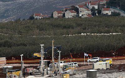 En esta foto del 13 de diciembre de 2018, el equipo militar israelí trabaja en la frontera libanesa-israelí frente a la ciudad israelí de Metula, al fondo, cerca de la aldea sureña de Kafr Kila, en el Líbano. (Foto AP / Hussein Malla)