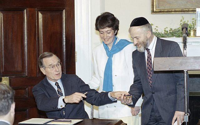 El presidente George HW Bush le entrega una pluma a Vladimir Raiz después de firmar un mensaje de Pascua en la Casa Blanca, Washington, el miércoles 4 de abril de 1990, mientras su esposa Karmella observa. Ambos habían emigrado recientemente de la Unión Soviética a Israel. (Foto AP / Barry Thumma)