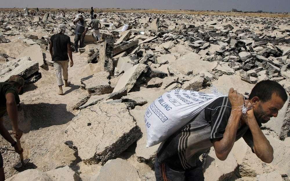 Los palestinos excavan en lo que una vez fue la pista del aeropuerto bombardeado de Gaza para recoger los escombros y la grava necesarios para la construcción en el territorio asolado por la guerra, en las afueras de Rafah, sur de la Franja de Gaza, 16 de agosto de 2010. (Foto AP / Khalil Hamra)