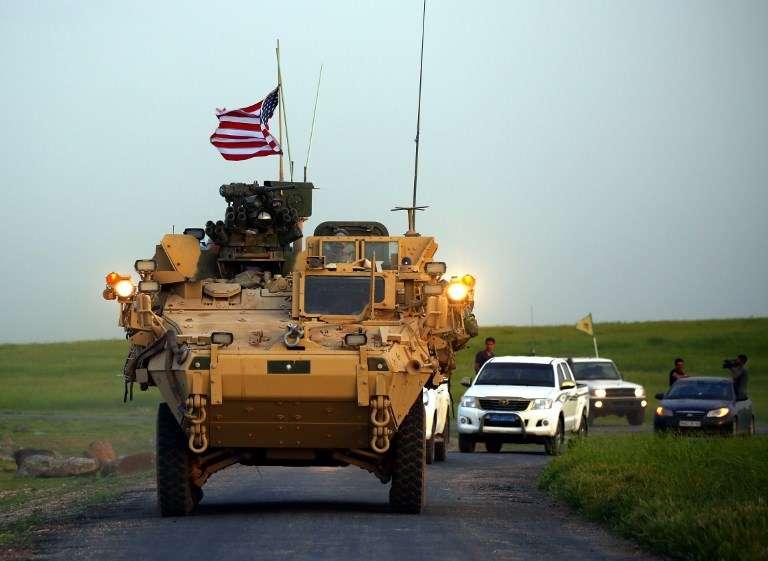 Las fuerzas estadounidenses, acompañadas por combatientes de las Unidades de Protección de los Pueblos Kurdos (YPG), conducen sus vehículos blindados cerca de la aldea siria de Darbasiyah, en la frontera con Turquía, 28 de abril de 2017. (DELIL SOULEIMAN / AFP)