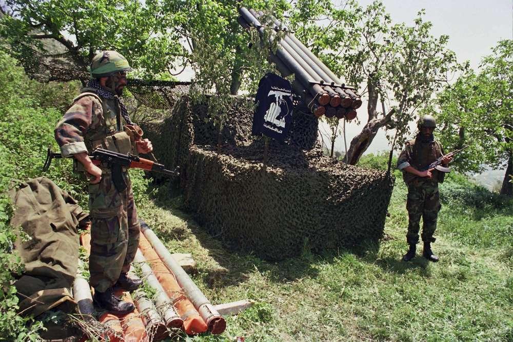 En esta foto del archivo de abril de 1996, dos combatientes de Hezbolá se colocan cerca de los cohetes Katyusha en el pueblo sureño de Ein Qana, Líbano (Foto AP / Mohammed Zaatari, archivo)