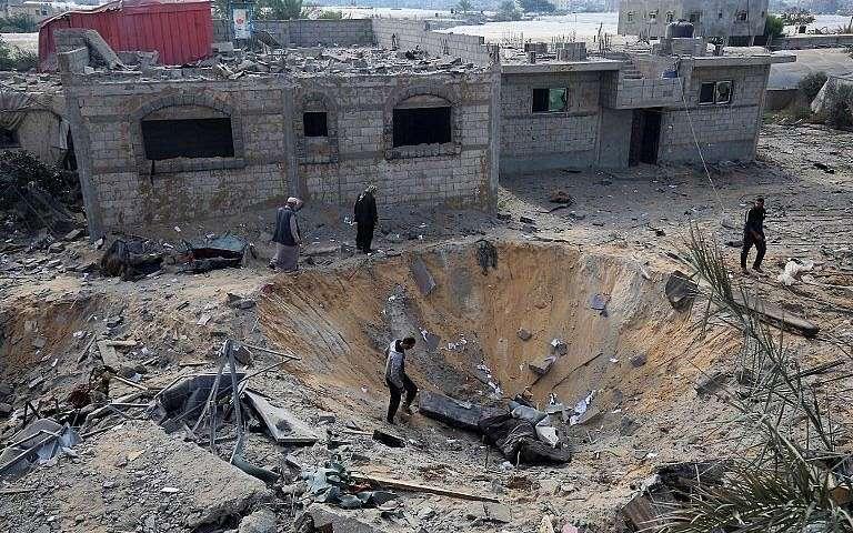 Árabes inspeccionan un cráter causado por un ataque aéreo israelí a principios de esta semana durante los combates con grupos terroristas palestinos, en Rafah, en el sur de la Franja de Gaza, el 14 de noviembre de 2018. (Said Khatib / AFP)