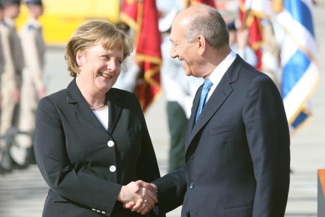 La canciller alemana y presidenta de la Unión Europea, Angela Merkel, y el primer ministro israelí, Ehud Olmert, asisten a una ceremonia de bienvenida el 16 de marzo de 2008 en el Aeropuerto Internacional Ben-Gurion. Crédito: Yossi Zamir / Flash90.