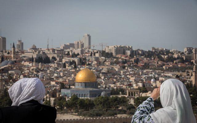 Los turistas miran la vista de la Cúpula de la Roca y el Monte del Templo desde el mirador del Monte de los Olivos que domina la ciudad vieja de Jerusalén, el 28 de noviembre de 2018. (Yonatan Sindel / Flash90)