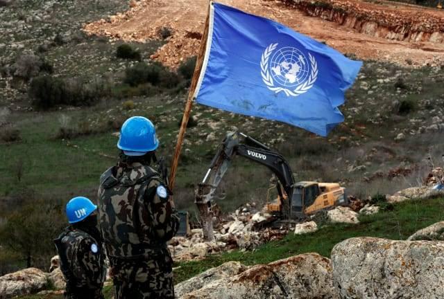 El personal de mantenimiento de la paz de la ONU sostiene su bandera, mientras observan a los excavadores israelíes trabajando cerca de la aldea fronteriza del sur de Mays al-Jabal, Líbano, el 13 de diciembre de 2018.Hussein Malla / AP