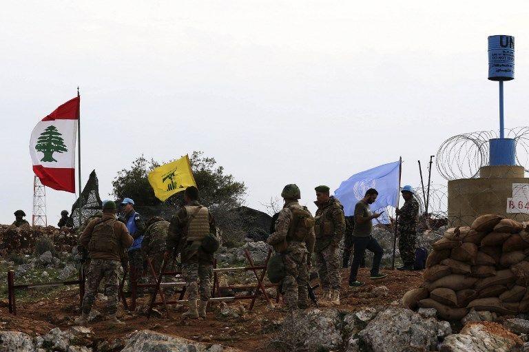 Una fotografía tomada desde la aldea sur de Líbano, Meiss al-Jabal, el 16 de diciembre de 2018, muestra a soldados israelíes observando a los soldados de las Fuerzas Provisionales de las Naciones Unidas en el Líbano (UNIFIL) hablar con soldados libaneses frente a una bandera de Hezbolá.(Mahmoud ZAYYAT / AFP)