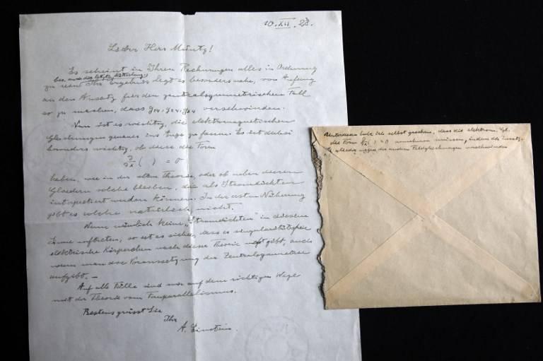 """Una fotografía tomada el 6 de marzo de 2018 muestra una carta firmada por el físico ganador del Premio Nobel Albert Einstein con fecha de 1928 sobre la formalización de la """"Tercera Etapa de la Teoría de la Relatividad"""" en exhibición en la casa de subastas Winner's en Jerusalén, antes de ser subastada posteriormente en la noche con el resto de una serie de nueve.(AFP PHOTO / MENAHEM KAHANA)"""