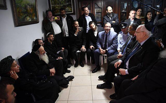 El presidente Reuven Rivlin, a la derecha, visita a la familia del soldado Yosef Cohen, asesinado en un ataque terrorista en el cruce de Givat Assad en la Ribera Occidental, en Jerusalén, el 18 de diciembre de 2018. (Haim Zach / GPO)