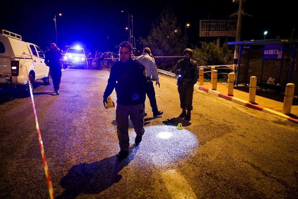 Los soldados y la policía israelíes inspeccionan la escena de un ataque terrorista en la entrada del poblado israelí de Ofra en Cisjordania, el 9 de diciembre de 2018. (Ofer Meir / Flash 90)