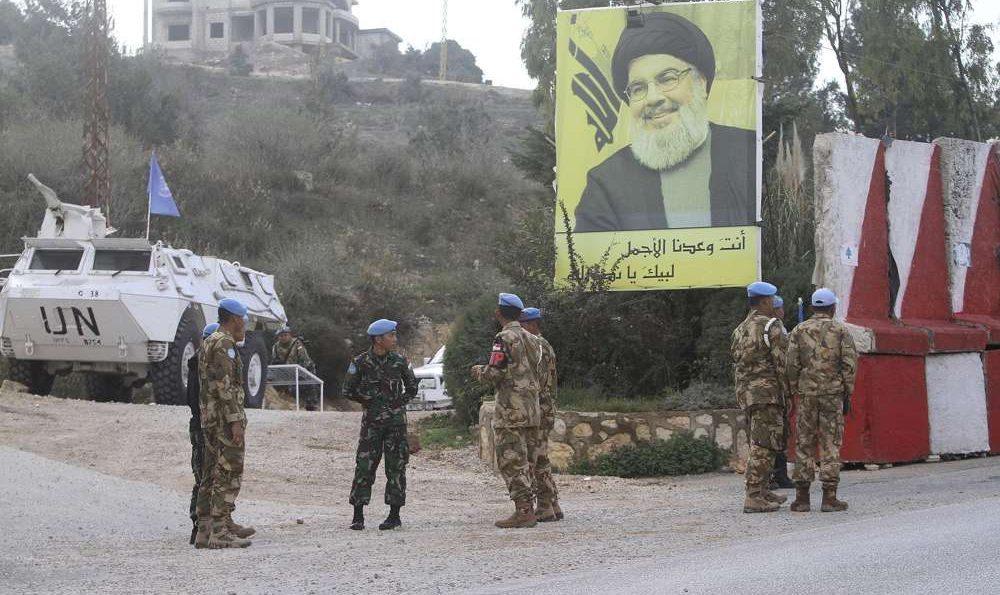 El personal de mantenimiento de la paz de la ONU de Indonesia está frente a un cartel del líder de Hezbolá, Sheikh Hassan Nasrallah, mientras patrullan el lado libanés de la frontera libanés-israelí en la aldea sur de Kfar Kila, Líbano, 4 de diciembre de 2018. (AP / Mohammed Zaatari)