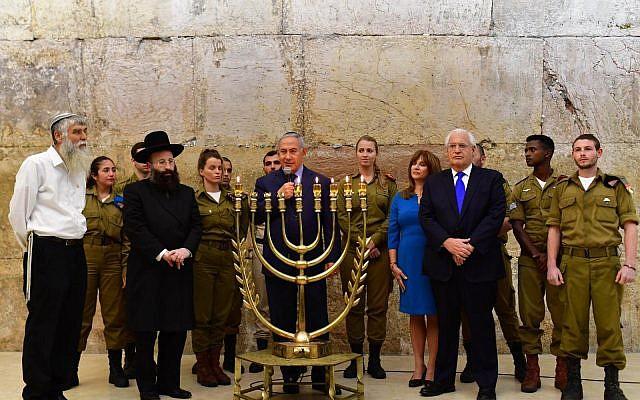El primer ministro Benjamin Netanyahu se unió al embajador de los Estados Unidos en Israel, David M. Friedman, y a su esposa Tammy en el Muro Occidental de Jerusalén para una ceremonia de encendido de velas que conmemora la quinta noche de Hanukkah con motivo de un año desde la declaración del 6 de diciembre de 2017 del presidente Trump sobre el traslado de EE. UU. Embajada en Jerusalem. (Koby Gideon / GPO)