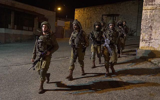 Soldados israelíes buscan a hombres armados que abrieron fuego en una parada de autobús fuera del asentamiento de Ofra en Cisjordania, hiriendo a siete personas, el 9 de diciembre de 2018. (Fuerzas de Defensa de Israel)