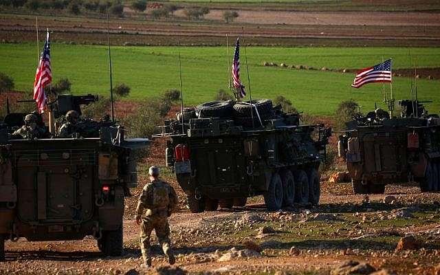 Los vehículos blindados de las fuerzas estadounidenses conducen cerca de la aldea de Yalanli, en las afueras del oeste de la ciudad de Manbij, en el norte de Siria, el 5 de marzo de 2017. (DELIL SOULEIMAN / AFP)