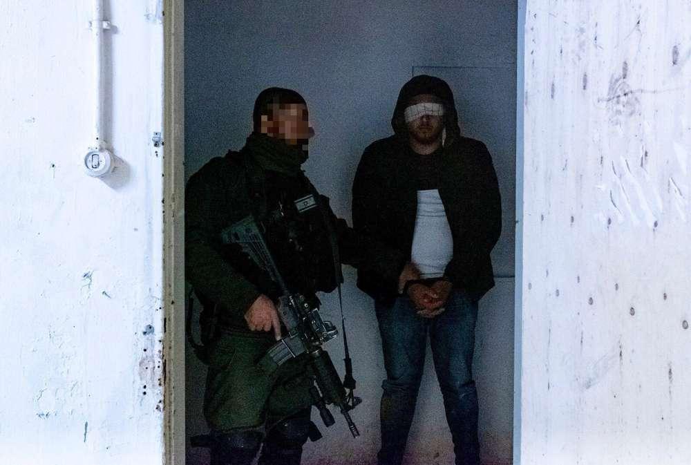 Tropas israelíes arrestan a un palestino, sospechoso de haber cometido un ataque a tiros en una parada de autobús frente al poblado de Ofra en Samaria, cerca de Ramallah, en el que siete israelíes resultaron heridos, incluida una mujer embarazada, a principios de la semana, en diciembre. 12, 2018. (Fuerzas de Defensa de Israel)
