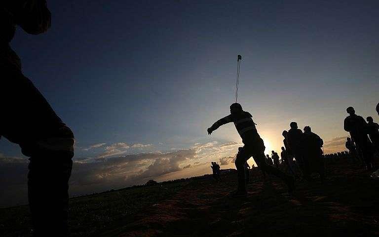 Un islamista palestino usa una honda para arrojar piedras durante la violenta manifestación islamista cerca de la frontera entre Israel y Khan Younis en el sur de la Franja de Gaza, el 21 de diciembre de 2018. (Said Khatib / AFP)