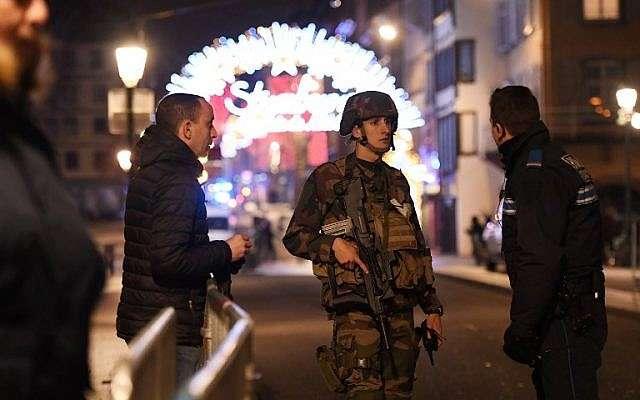 Policías hablan con un militar en las calles de Estrasburgo, en el este de Francia, después de un tiroteo, el 11 de diciembre de 2018. (Frederick FLORIN / AFP)