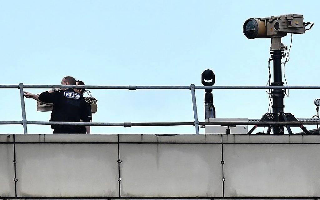 Oficiales de policía cerca del equipo en la azotea de un edificio en el aeropuerto de Londres Gatwick, al sur de Londres, el 21 de diciembre de 2018. (Ben Stansall / AFP)
