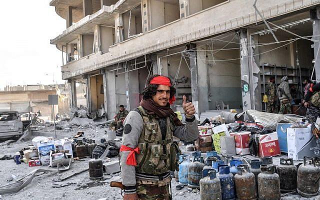 Los combatientes árabes sirios, respaldados por Turquía, saquean las tiendas después de tomar el control de la ciudad siria noroccidental de Afrin de las Unidades de Protección del Pueblo Kurdo (YPG) el 18 de marzo de 2018. (AFP PHOTO / BULENT KILIC)