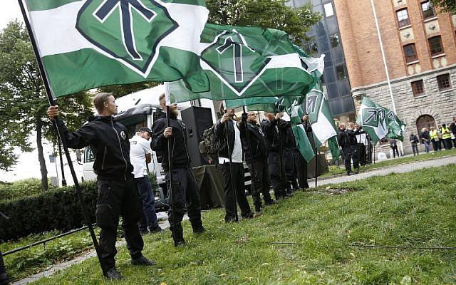 Los partidarios del Movimiento de Resistencia Nórdica neonazi tienen banderas durante una manifestación en la plaza Kungsholmstorg en Estocolmo, Suecia, el 25 de agosto de 2018. (Agencia de noticias AFP / TT / Fredrik Persson)