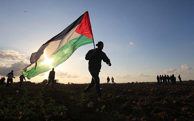 Un manifestante palestino porta una bandera nacional durante una manifestación cerca de la frontera entre Israel y Khan Yunis en el sur de la Franja de Gaza, el 21 de diciembre de 2018. (Foto de SAID KHATIB / AFP)
