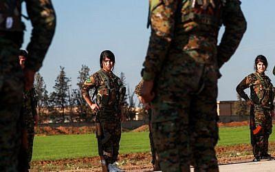 Combatientes de las unidades de protección de mujeres kurdas (YPJ) asisten al funeral de un combatiente árabe de las Fuerzas Democráticas Sirias (SDF) en la ciudad de Tal Tamr, en el campo de la provincia de Hasakeh, noreste de Siria, el 21 de diciembre de 2018. (Delil Souleiman / AFP )