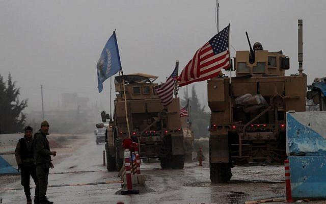 Una línea de vehículos militares de Estados Unidos atraviesa un puesto de control de las Fuerzas de Seguridad Internas en Manbij cuando se dirigen a su base en las afueras de la ciudad del norte de Siria el 30 de diciembre de 2018. (Delil SOULEIMAN / AFP)