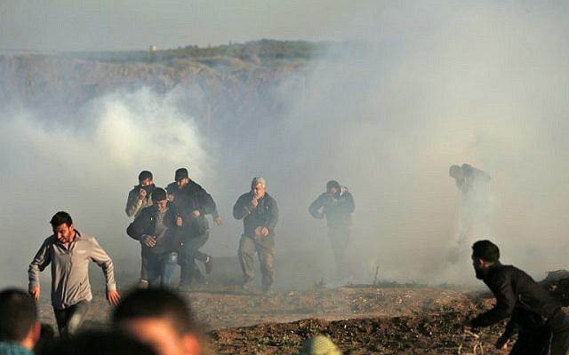 Los palestinos atraviesan humos de gas lacrimógeno durante los enfrentamientos con las fuerzas israelíes durante una manifestación a lo largo de la frontera con Israel al este de la ciudad de Gaza el 11 de enero de 2019. (Foto de MAHMUD HAMS / AFP)