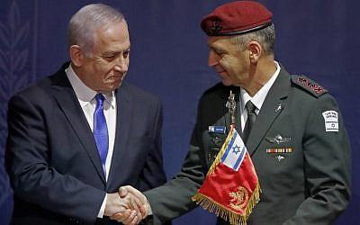 El jefe de personal entrante de las FDI, Aviv Kohavi, le da la mano al primer ministro Benjamin Netanyahu durante una ceremonia de entrega el 15 de enero de 2019, en la sede del Ministerio de Defensa en Tel Aviv. (Jack Guez / AFP)