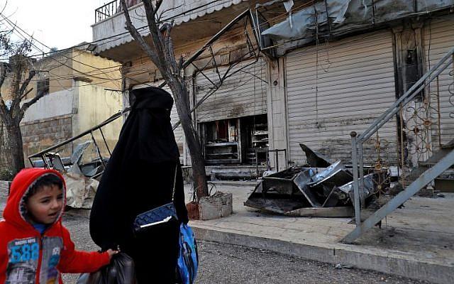 Una mujer y un niño sirios pasan frente a las puertas cerradas de un restaurante donde se produjo un ataque suicida contra las fuerzas de la coalición liderada por Estados Unidos en la ciudad de Manbij, en el norte de Siria, que mató a cuatro militares estadounidenses el día anterior el 17 de enero de 2019. Delil SOULEIMAN / AFP)