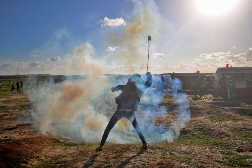 Un palestino usa una honda para lanzar gases lacrimógenos contra las fuerzas israelíes durante una manifestación en la cerca israelí al este de la ciudad de Gaza el 18 de enero de 2019. (Dijo KHATIB / AFP)