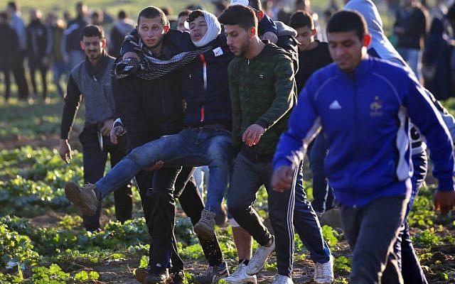 Los palestinos se llevan a un manifestante herido durante los enfrentamientos con las fuerzas israelíes en una manifestación en la frontera con Israel al este de la ciudad de Gaza el 18 de enero de 2019. (Dijo KHATIB / AFP)