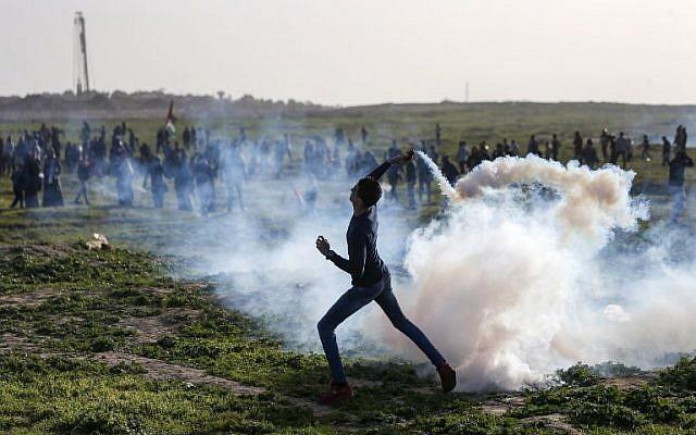 n palestino lanza un bote de gas lacrimógeno hacia las fuerzas israelíes durante los enfrentamientos en la frontera con Israel, al este de la ciudad de Gaza, el 25 de enero de 2019. (Mahmud Hams / AFP)