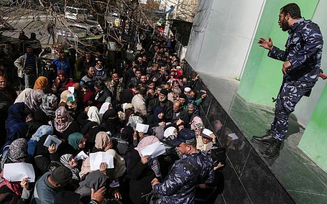 Las fuerzas de seguridad leales a Hamas organizan una línea fuera de la oficina central de correos en la ciudad de Gaza el 26 de enero de 2019, mientras los palestinos se reúnen para recibir ayuda financiera del gobierno de Qatar, que se otorga a familias empobrecidas. (Mahmud Hams / AFP)