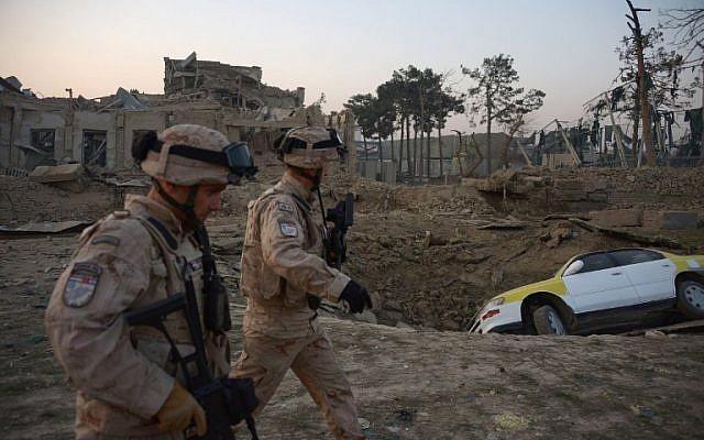 Soldados croatas de la coalición de la OTAN pasan frente a un cráter de una explosión de bomba mientras inspeccionan el sitio de un ataque al consulado alemán en Mazar-i-Sharif, Afganistán, el 11 de noviembre de 2016. (AFP / Farshad Usyan)