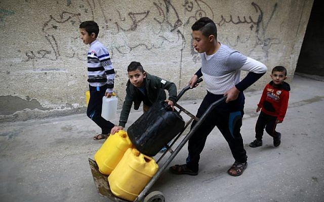 Los niños palestinos cargan botellas de agua en el campamento de refugiados de al-Shati en la ciudad de Gaza el 4 de enero de 2018. (AFP PHOTO / MOHAMMED ABED)
