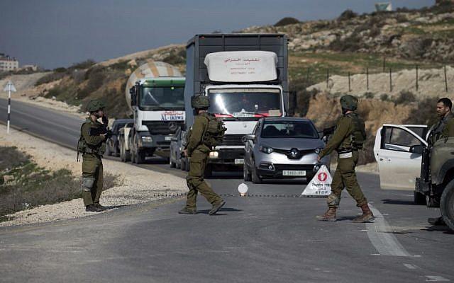 Ilustrativo: los soldados israelíes inspeccionan automóviles en un punto de control cerca de la ciudad de Nablus en Cisjordania el 10 de enero de 2018. (Jaafar / Ashtiyeh / AFP)