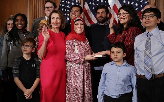 Rashida Tlaib (en thobe rojo y gafas), acompañada por su familia, jurando con la Presidenta de la Cámara de Representantes Nancy Pelosi (con vestido rosa), en el Capitolio de los Estados Unidos en Washington, DC, 3 de enero de 2019. (Chip Somodevilla / Getty Imágenes / AFP)