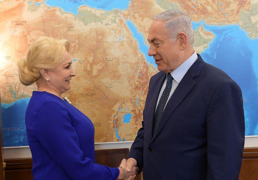 El primer ministro Benjamin Netanyahu da la mano al primer ministro rumano, Viorica Dăncilă. (Crédito de la foto: AMOS BEN-GERSHOM / GPO)