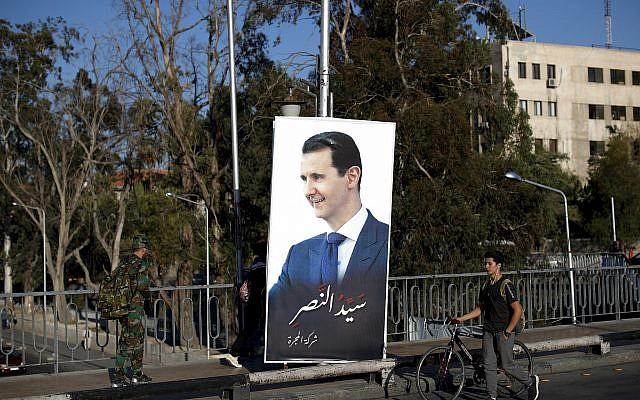 """Los sirios pasan por un póster del presidente Bashar Assad con un árabe que dice: """"Maestro de la victoria"""", cuelga de un puente en la capital siria, Damasco, Siria, 14 de julio de 2018. (Hassan Ammar / AP)"""