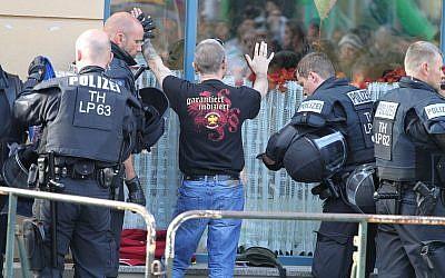 """En esta foto del 6 de octubre de 2018, los oficiales de policía buscan a un visitante de un concierto de rock neo-nazi en Aploda, Alemania. El eslogan en la camiseta dice """"garantizado indexado"""". (Sebastian Haak / dpa via AP)"""