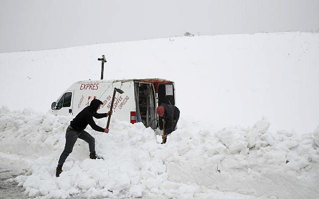 Dos sirios quitan la nieve, para abrir un camino a su camioneta donde venden bebidas calientes, en el costado de una carretera en el pueblo de Mdeirij, en el Monte Líbano, el 9 de enero de 2019. (Foto AP / Bilal Hussein)