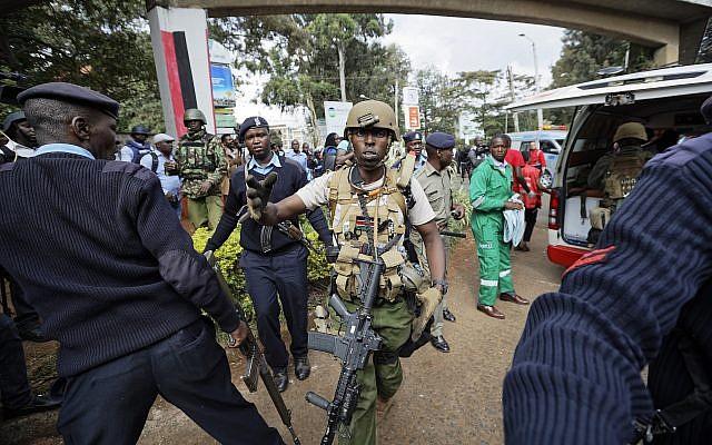 Un miembro de las fuerzas especiales de Kenia les grita a los medios que se retiren después de que su herido colega fue llevado a una ambulancia por paramédicos en la escena el 16 de enero de 2019 en Nairobi, Kenia. (Foto AP / Ben Curtis)