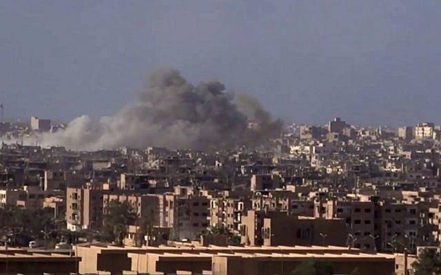 Archivo: Humo y escombros en aumento después del bombardeo del gobierno sirio de la ciudad de Deir el-Zour durante una batalla contra el Estado Islámico en 2017 (SANA a través de AP)