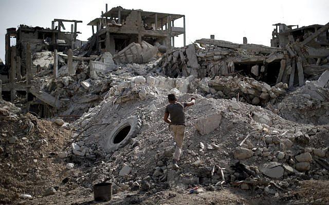 Un joven camina a través de los escombros en el campamento de refugiados palestinos de Yarmouk, en la capital siria, Damasco, Siria, 6 de octubre de 2018 (AP Photo / Hassan Ammar)