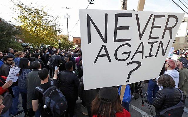 Una persona sostiene un cartel durante una reunión de protesta en el bloque del Centro Comunitario Judío en el vecindario de Squirrel Hill en Pittsburgh, donde se realizó el funeral del Dr. Jerry Rabinowitz, el martes 30 de octubre de 2018. (AP / Gene J. Puskar)